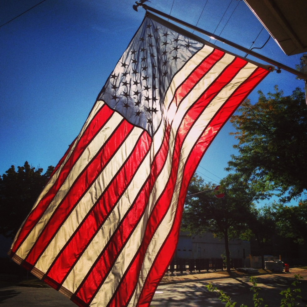 sun shining through the flag hanging proudly from my porch