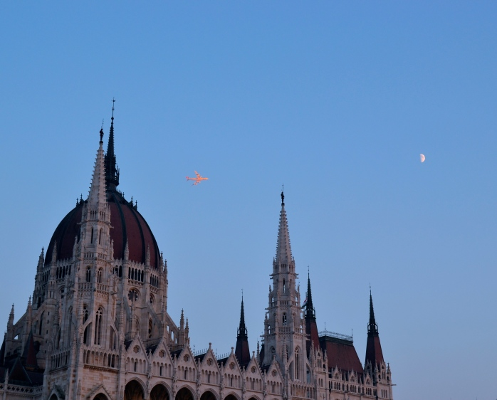 Plane flying directly into the sunset, over the Parliament, Budapest